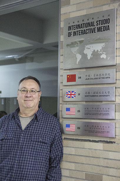Joseph Scheer with International Studio of Interactive Media sign
