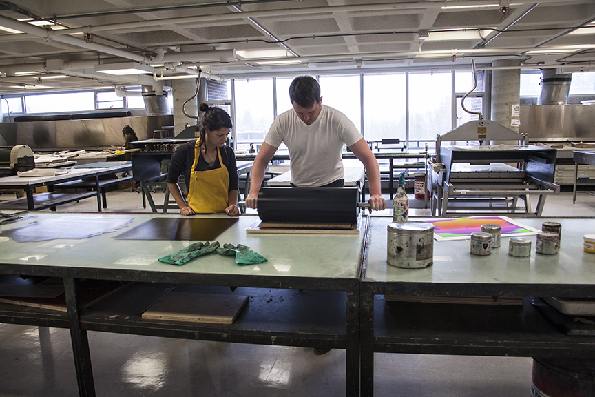 Jax and Kyle inking and preparing a woodblock for printing.