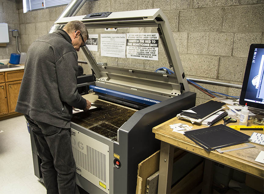 Scott unloading book pieves from the laser cutter