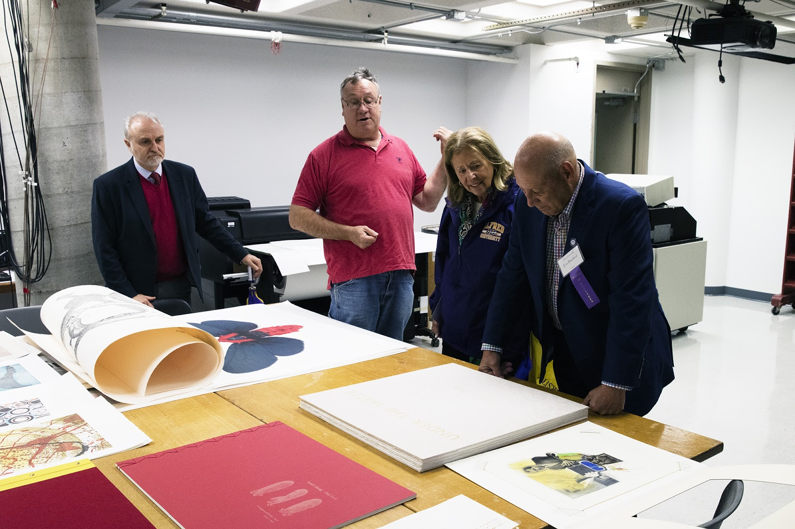 (left to right) School of Art & Design Dean Gerar Edizel, IEA Co-Director Joseph Scheer, and Alfred University Trustees Susan and Eric Bershad looking at an artist book made by Zihao Chen (BFA 2013), a former student of Joseph Scheer.