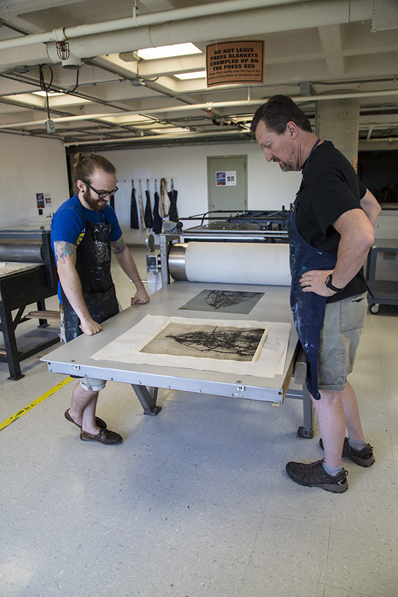 Bob (right) with print technical specialist Tim Pauszek examining a polymer plate print