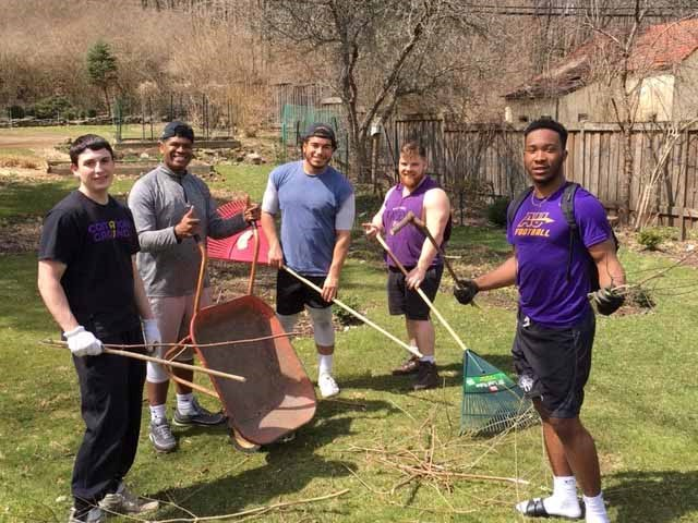From left, Joe Borrelli '22, Xavier Spencer '22, Justin Mosley '18, Russ Kohler '20 and Variotho Nicolas '22 doing yard work on a football day of service