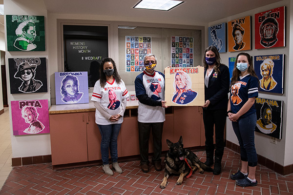 From left: Nadine Shardlow; President Mark Zupan; Kristin Beck (holding the mosaic portraying Beck); and Genevieve Greene. Kristin's dog, Sargent, is in the foreground.